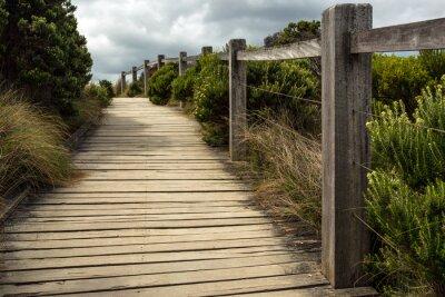 Papiers peints Une passerelle en bois le long d'une clôture avec la végétation verte croissante des deux côtés sous un ciel nuageux. C'est situé quelque part le long de la grande route de l'océan en Australie.