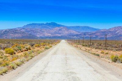 Papiers peints Une route de terre dans le Karoo courir à côté des clôtures de ferme.