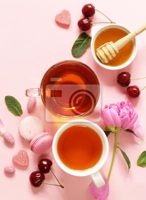 Une tasse de thé pour une femme, un macaron, des fleurs et des bonbons sur fond rose