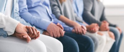 Papiers peints Unrecognizable people sitting in row and holding hands during therapy session