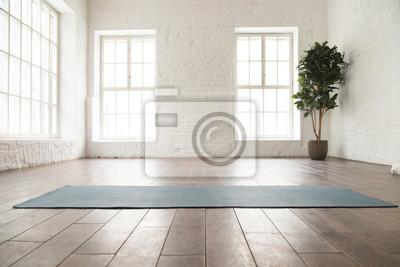 Papiers peints Unrolled yoga mat on wooden floor in yoga studio