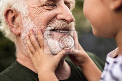Papiers peints Vieil homme souriant et sa petite fille se regardant