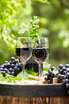 Vieux tonneau en bois avec une bouteille et un verre de vin rouge.