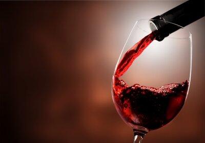 Papiers peints Vin rouge versé dans un verre sur fond