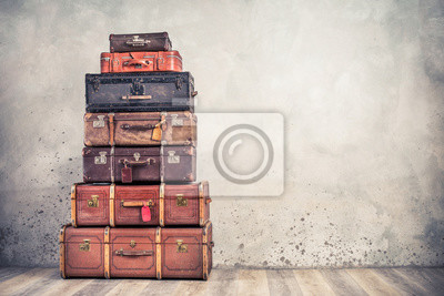Papiers peints Vintage classic outdated trunks luggage with tags, old antique leather suitcases tower front concrete wall background. Travel baggage concept. Retro style filtered photo