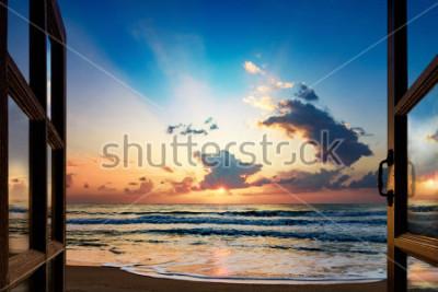 Papiers peints Vue du lever du soleil sur la mer depuis la fenêtre ouverte
