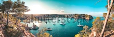 Papiers peints Vue panoramique d'une baie de la plage aux eaux bleu turquoise et voiliers et yachts à l'ancre avec pins encadrés. Belle romantique Cala Portals Vells, Majorque, Espagne. les Îles Baléares