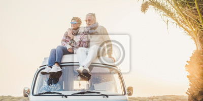 Papiers peints Wanderlust and travel destination happiness concept with old senior beautiful couple sitting and enjoying the outdoor freedom on the roof of vintage van vehicle together - sun backlight