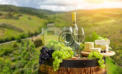 wine bottle and wine glass on wodden barrel. Beautiful Tuscany background