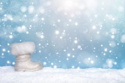 Winter seasonal background with the boot of santa and snow and snow flakes