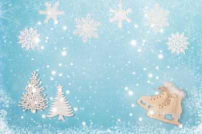 Winter seasonal flatlay with the ice skates and christmas trees on a blue background with and snow and snow flakes