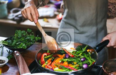 Papiers peints Woman cooking stir fried vegetables