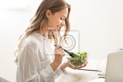 Papiers peints Woman eating healthy vegetable salad in office