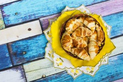 Papiers peints Самодельные круассаны в плетеной корзинке на желтой салфетке с цветочным узором на старом / вытертом полу