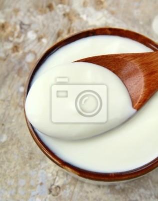 yaourt nature fraîche dans une tasse en céramique sur table en bois