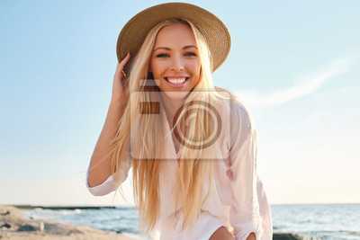 Papiers peints Young attractive smiling blond woman in shirt and hat joyfully looking in camera with sea on background