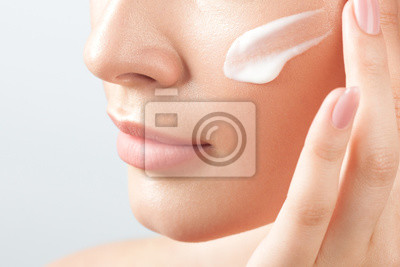 Papiers peints Young beautiful woman applies cream on clean perfect skin