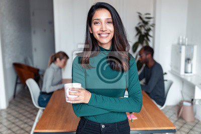 Papiers peints Young indian business woman entrepreneur looking at camera in the office.