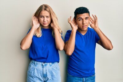 Papiers peints Young interracial couple wearing casual clothes trying to hear both hands on ear gesture, curious for gossip. hearing problem, deaf