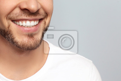 Papiers peints Young man with beautiful smile on grey background. Teeth whitening