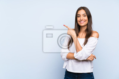 Papiers peints Young woman over isolated blue background pointing finger to the side
