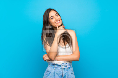 Papiers peints Young woman over isolated blue background smiling