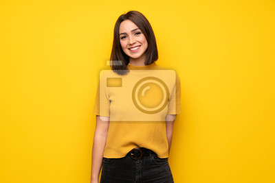Papiers peints Young woman over yellow wall smiling