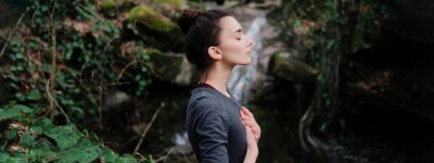 Papiers peints Young woman practicing breathing yoga pranayama outdoors in moss forest on background of waterfall. Unity with nature concept.