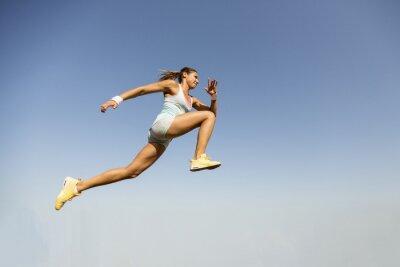 Papiers peints Young woman taking long jump