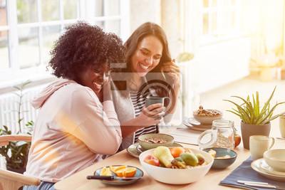 Papiers peints Zwei glückliche Frauen essen Frühstück à Küche