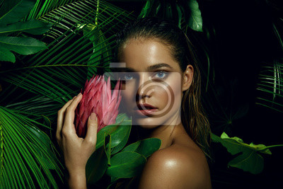 Posters A beautiful tanned girl with natural make-up and wet hair stands in the jungle among exotic plants.
