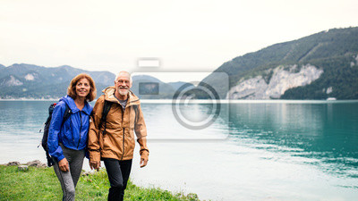 Posters A senior pensioner couple hiking by lake in nature, holding hands.