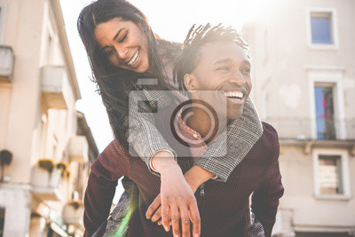 Posters African couple having fun outdoor in city tour - Young people lovers enjoying time together during vacation journey - Love, fashion, travel and relationship concept - Focus on woman face