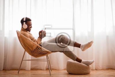 Posters Afro Guy In Headphones Using Smartphone Sitting On Chair Indoor