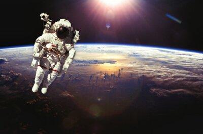 Posters Astronaute dans l'espace au-dessus de la terre au coucher du soleil. Elements