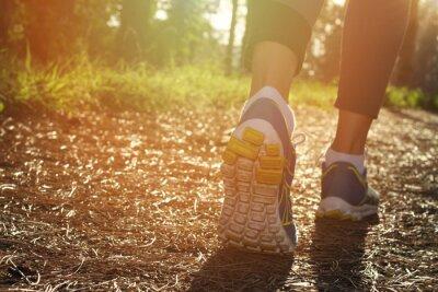 Posters Athlète coureur pieds en cours d'exécution dans la nature, gros plan sur les chaussures. Femme de remise en forme le jogging, le concept de style de vie actif