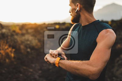 Posters Athletic runner start training on fitness tracker or smart watch and looking forward on horizon. Trail running and active lifestyle concept.