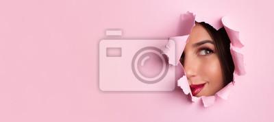 Posters Bannière publicitaire de salon de beauté avec espace de copie. Belle fille regarde à travers le trou dans le fond de papier rose. Maquilleur, mode, concept de beauté. Vente de cosmétiques.