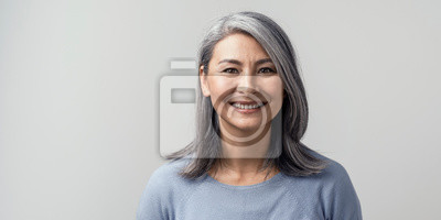 Posters Beautiful asian with grey hair smiling standing near the wall