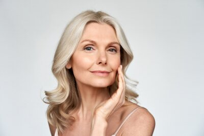 Posters Beautiful gorgeous 50s mid aged mature woman looking at camera isolated on white. Mature old lady close up portrait. Healthy face skin care beauty, middle age skincare cosmetics, cosmetology concept