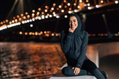 Posters Beautiful middle east woman in hoodie sitting on embankment at night and resting after workout
