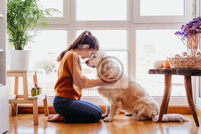 Posters beautiful woman hugging her adorable golden retriever dog at home. love for animals concept. lifestyle indoors