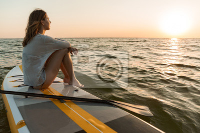Posters Beautiful young woman sitting on a stand up paddle board