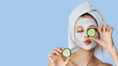 Posters Beautiful young woman with facial mask on her face holding slices of cucumber. Skin care and treatment, spa, natural beauty and cosmetology concept.
