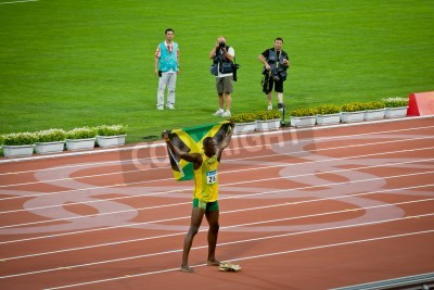 Posters Beijing - Aug 16: Usain Bolt celebrates holding the Jamaican flag after setting new world 100 meter record  for men