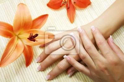 Belles mains avec un bon mensonge de manucure près de lys lumineux