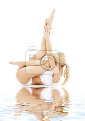 blonde en sous-vêtements blanc en forme à pratiquer le yoga sur le sable blanc