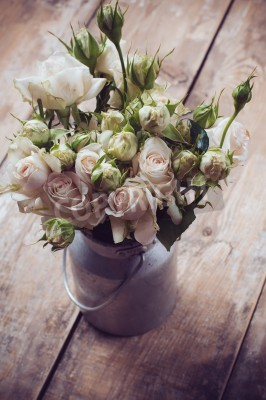 Posters Bouquet of roses in metal pot on the wooden background, vintage style