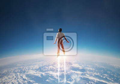 Posters Businessman in suit and aviator hat flying in sky