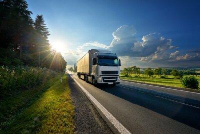 Posters Camion blanc arrivant sur la route goudronnée dans un paysage rural dans les rayons du soleil couchant